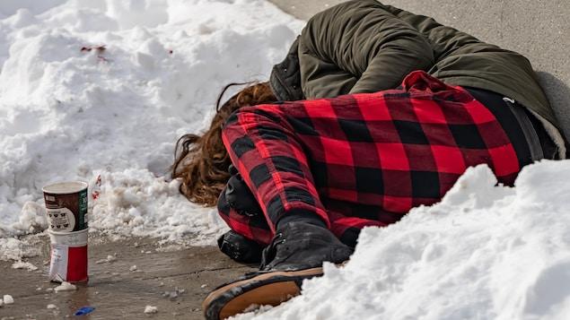 Un itinérant couché sur le sol, entouré de neige à Ottawa. Près de lui, une vieille tasse à café à usage unique.