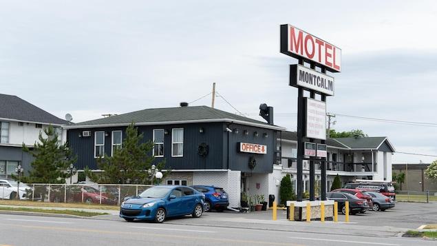 Un motel vu de l'extérieur avec des voitures stationnées devant.
