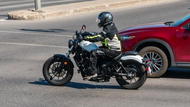 Un motocycliste circule dans la rue.