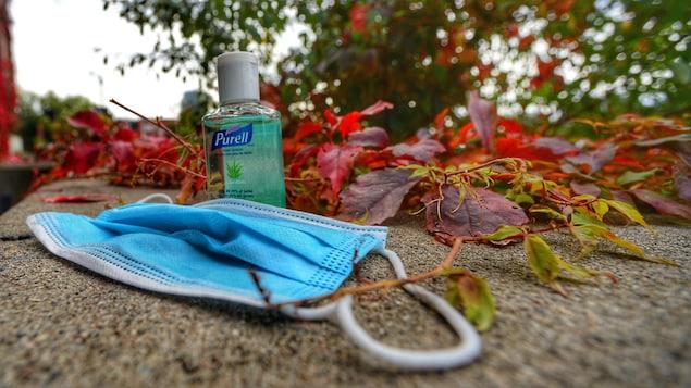 Nature morte avec un masque hygiénique et une bouteille de désinfectant dans les feuilles d'automne.