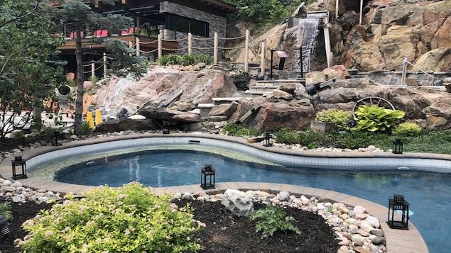 Un spa extérieur dans un environnement luxueux avec des chutes