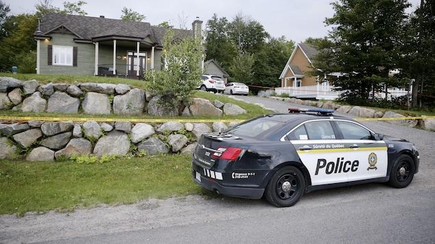 Une voiture de police devant un périmètre de sécurité.