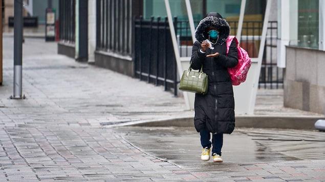 Une femme portant un masque se désinfecte les mains dans la rue