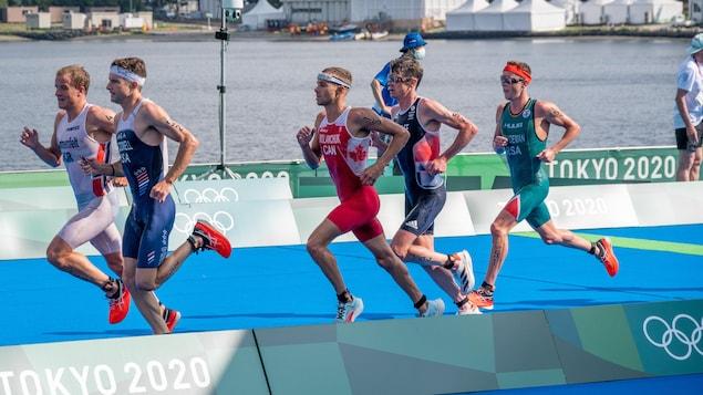 Un homme en rouge et en blanc avec une feuille d'érable court au milieu d'un peloton d'athlètes près d'un plan d'eau.