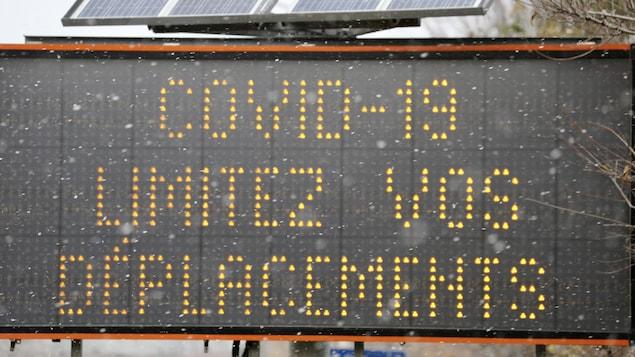 Une affiche routière avec les mots Covid-19 limitez vous déplacements