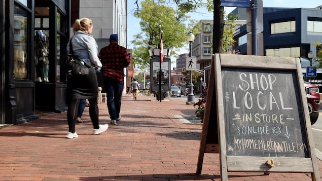 Des passants sur le trottoir devant des commerces.