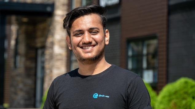 Shubham Mavani, un jeune homme souriant, devant un édifice.