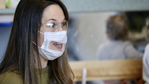 Une femme porte un masque à fenêtre transparente.