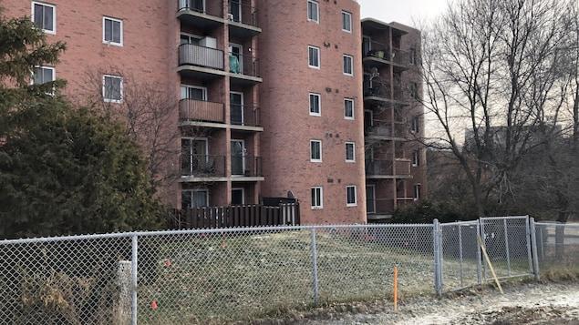 Un bâtiment de briques roses sur un terrain clôturé.