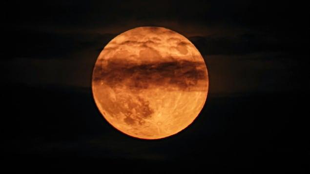 Une pleine lune orange couverte par quelques nuages