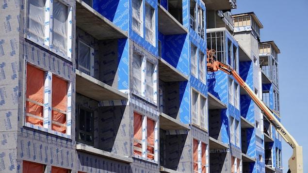 Une grue et un immeuble résidentiel en construction au Nouveau-Brunswick en mars 2020.