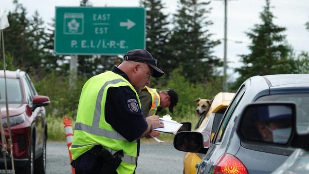 Un policier parle avec un automobiliste avec en arrière-plan une pancarte de l'Île-du-Prince-Édouard
