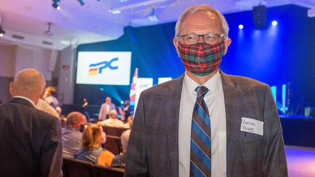 Blaine Higgs en complet et cravate porte sur le nez et la bouche un masque non médical en tissu à carreaux rouges et verts.