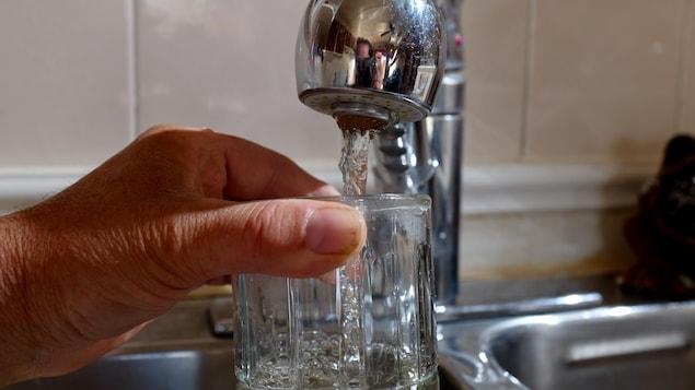 Une main tient un verre et le remplit d'eau du robinet.
