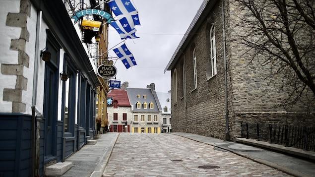 Le quartier Petit Champlain avec le drapeau québécois sur les façades est vide de monde.