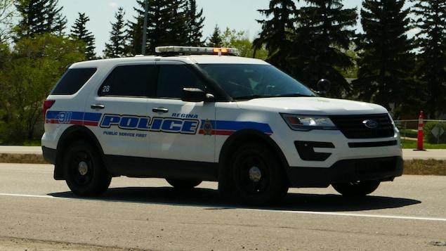 Une voiture de police circule sur une route.