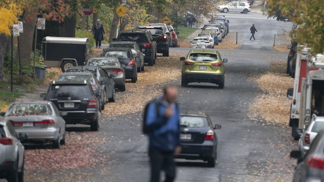 Des gens traversent une rue d'un quartier résidentiel.