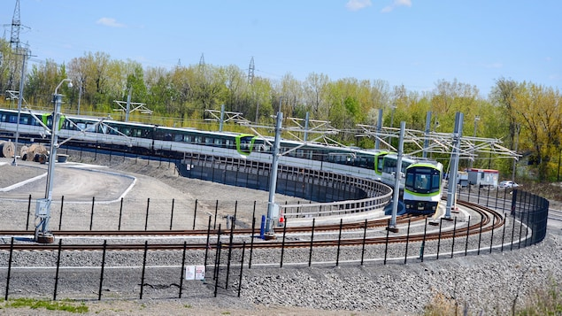 Des wagons du REM circulent sur une voie.