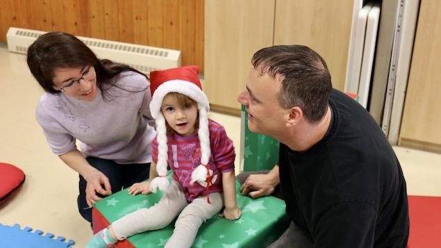 Des parents qui jouent avec leur enfant dans les locaux d'un organisme communautaire de Québec.