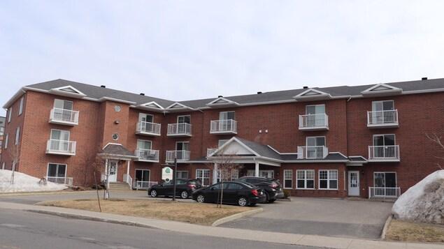 Un édifice, de trois étages aux briques rouges, qui regroupe des chambres pour personnes âgés. C'est l'hiver, le ciel est dégagé.