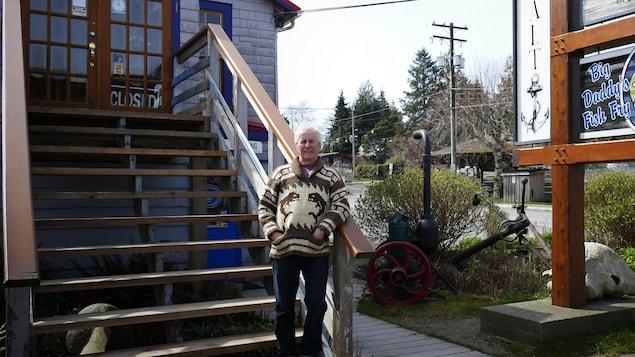 L'homme de 68 ans pose devant un bâtiment qu'il possède.