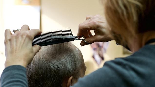 Charline LeBlanc coupe des cheveux en portant un masque.