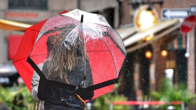 Des gens se promènent avec des parapluies.