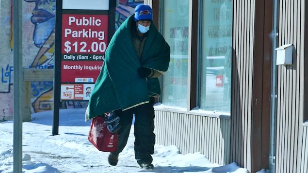 Un personne portant un masque est emmitouflé dans une couverture pour se protéger du froid à Regina, en Saskatchewan.