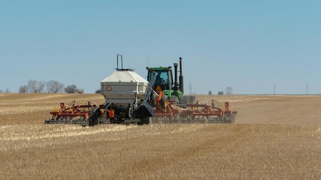 Un tracteur ensemence un champ.