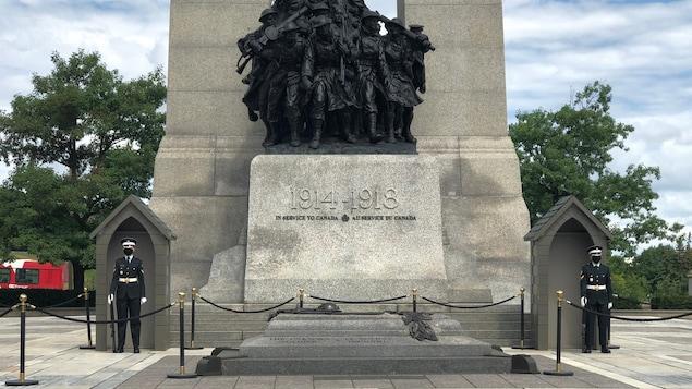 Deux soldats portant un masque sont placés sur les côtés du Monument commémoratif de guerre.
