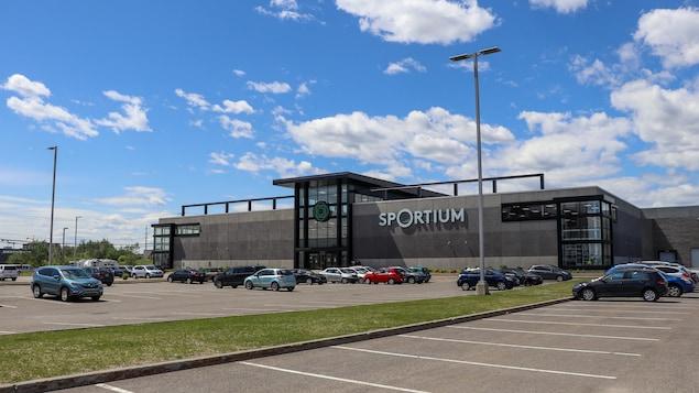 Le magasin Sportium de Québec en été, sous un ciel dégagé, avec plusieurs voitures stationnées dans le stationnement.