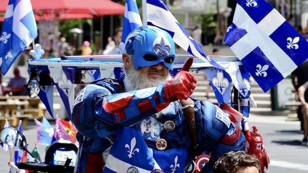 Un homme est couvert de drapeaux québécois.
