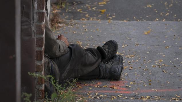 Un sans-abri est assis sur le trottoir, adossé à un mur de brique, en automne.