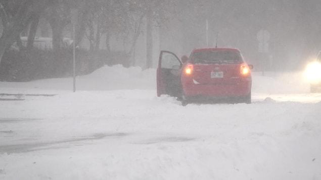 Le conducteur d'une voiture ouvre sa porte alors que son véhicule semble coincé dans un petit banc de neige pendant une tempête.