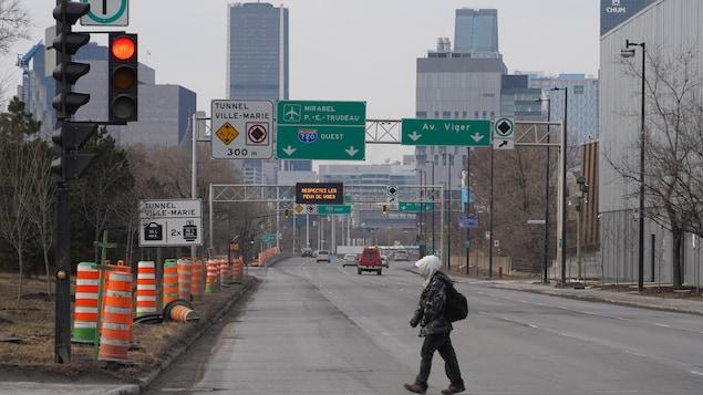 Une personne traverse une large voie de circulation à Montréal.
