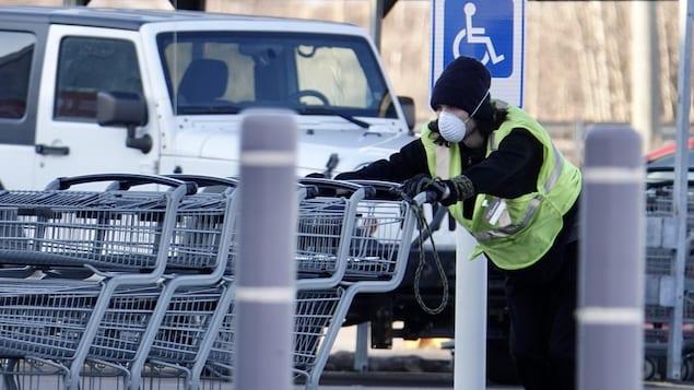 Un travailleur portant un masque pousse des paniers d'épicerie.