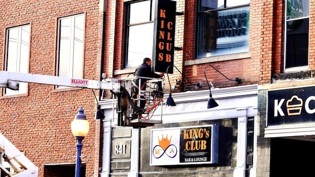 Un travailleur installe une affiche unilingue sur la rue Main à Moncton en janvier 2021.