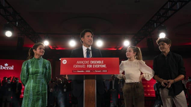 Wide shot of Justin Trudeau with his wife and children on stage for victory speech.