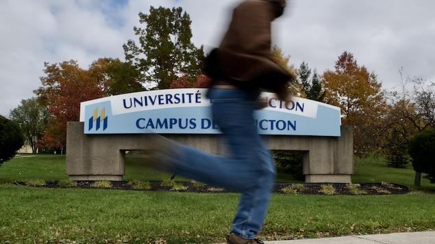 Un homme passe en courant devant l'enseigne du campus de Moncton.
