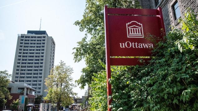 """Affiche """"uOttawa"""" près d'un édifice."""