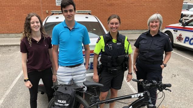 Les étudiants Saida Well et Sheldon Kilroy, et policières Hélène Boissonneault et Haley Field devant un vélo électrique.
