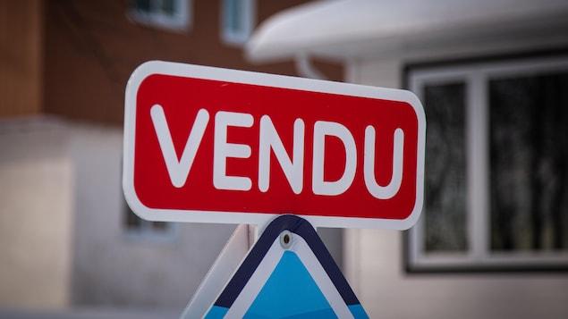 Carton « vendu » installé sur une affiche de courtier immobilier