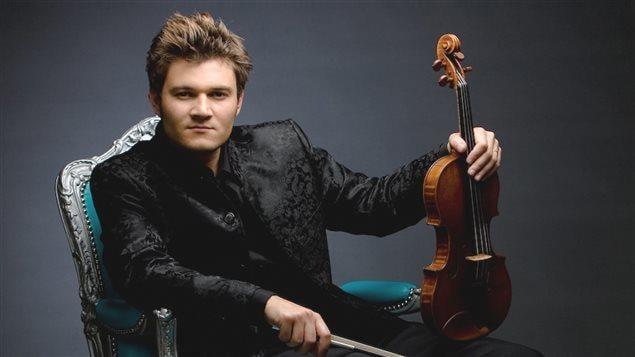 Il est assis sur une chaise au coussinage bleu-turquoise de style ancien, le violon debout sur un genou, en costume noir.