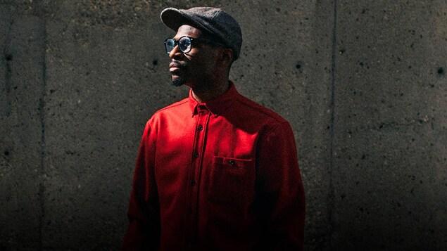 Alpha Toshineza, casquette, lunettes et portant une chemise rouge. Il regarde vers la gauche. Mur de béton derrière lui.