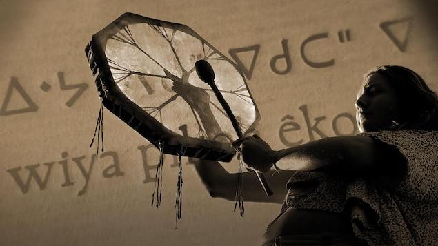 Une femme autochtone jouant du tambour; en arrière-plan, un texte écrit en cri.