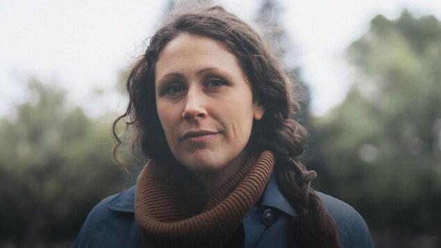 L'auteure-compositrice Belle Grand Fille (Anne-Sophie Doré-Coulombe) à l'extérieur par un temps plutôt gris. L'arrière plan est flou, mais on peut apercevoir des arbres.