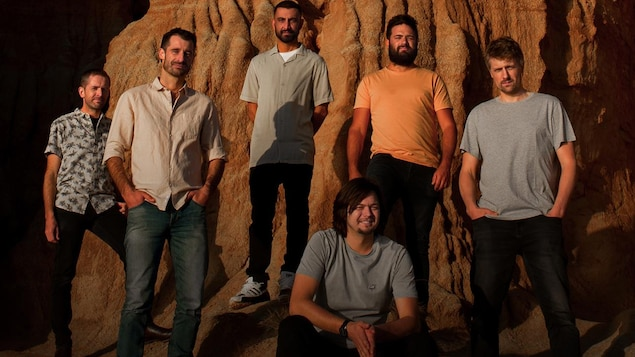 Le groupe The Cat Empire, composé de six membres, prend la pose devant une falaise.