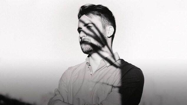 Photo en noir et blanc de Cédrik St-Onge; il semble avoir des ombres de minces palmes d'arbre au visage.