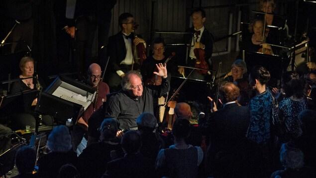 Ovation debout pour Maestro James Levine, qui salue le public. Il est entouré des musiciens de l'orchestre du Met.