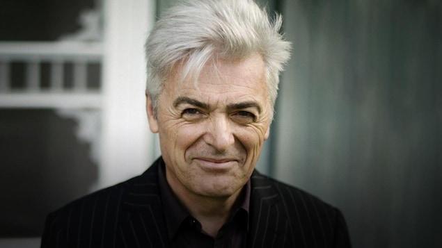 Un Daniel Lavoie souriant devant un arrière-plan gris et blanc très neutre